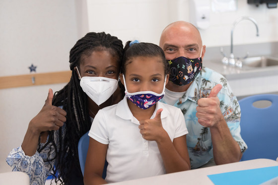 Family in masks giving a thumbs up sign.