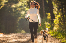 Woman running with dog on leash