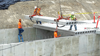 Workers use large cranes to help set lid covers for a massive cement storm retention vault at Seaway Transit Center