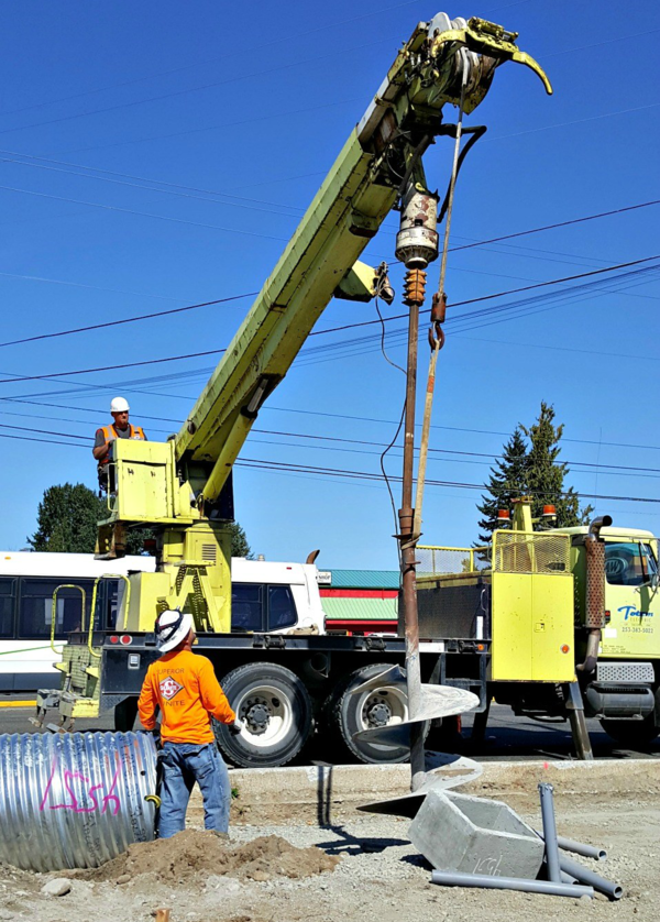 "Construction crews use an 11-foot long ""drill bit"" to bore a hole for a future electronic street sign."