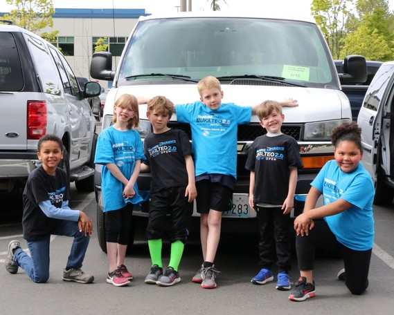 Kids from the Mukilteo and Edmonds Boys & Girls Clubs pose in front of a van awarded via the 2019 VanGO program.