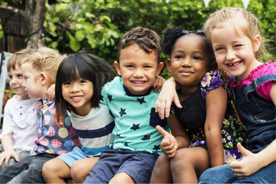 Children smiling with their arms around each other.