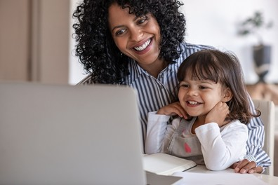 Mom and daughter smile while looking at a computer.