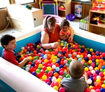Sarah in a ball pit with the kiddos
