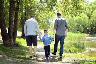 Same-sex couple walk hand in hand with their child in a park.
