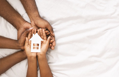Family holds hands together with a small paper house in their palms.
