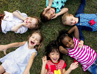 A group of young children smiling in the grass.