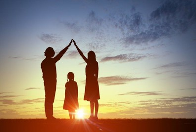 Two adults bridge their arms over a child, silhouetted against a warm sunset.