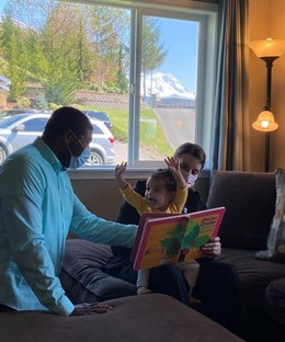 Two child care providers read to a young, excited toddler