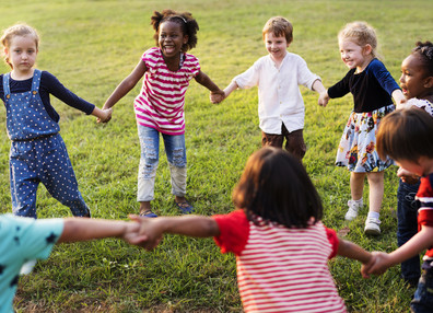 Children holding hands and playing in the park.
