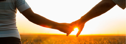 Child and parent hold hands in a meadow with warm sunset.