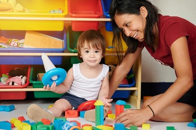 Small child with caregiver in child care setting.