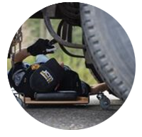 Image of state patrol under truck inspecting brakes