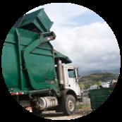 Image of dump truck lifting trash bin over truck