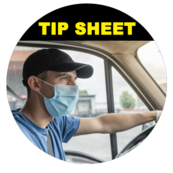 Image of truck driver holding steering wheel wearing a mask and gloves.