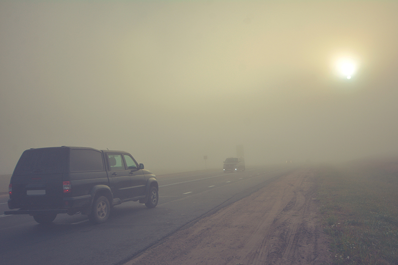 A truck drives through smog from forest fires.