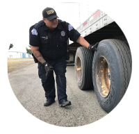 Image of a Washington State Patrol Commercial Vehicle Enforcement Officer inspecting a trailer.
