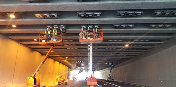 Construction workers replace light bulbs under a highway lid.