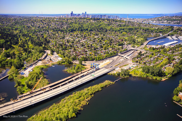 An aerial view of a highway that crosses water into a residential neighborhood. There is a city in the background.