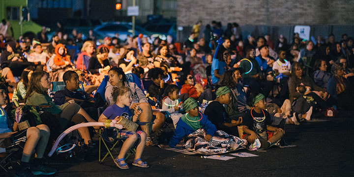 People watch an outdoor movie.