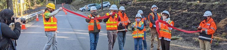 Dignitaries in hard hats and safety vests cut a red ribbon across a road
