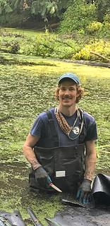 man cutting weeds in pond