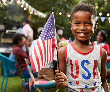 African American boy with flag and USA shirt at family barbecue