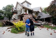 Photo of home destroyed by earthquake with couple standing outside