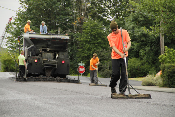 worker brooms slurry on roadway