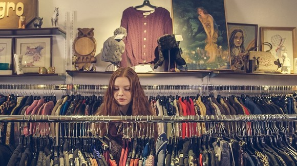 girl looking at second-use clothes on rack