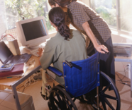 man in wheelchair at computer receiving assistance