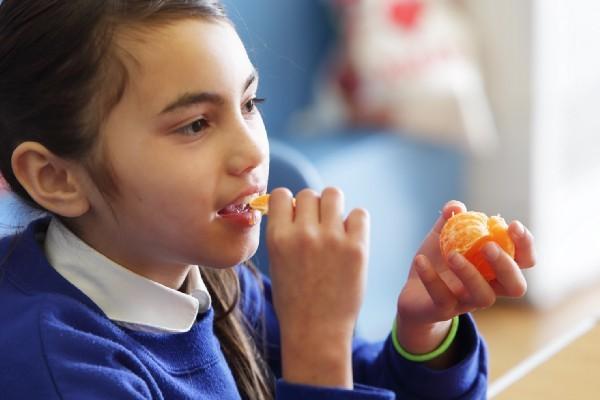 A student eats an orange