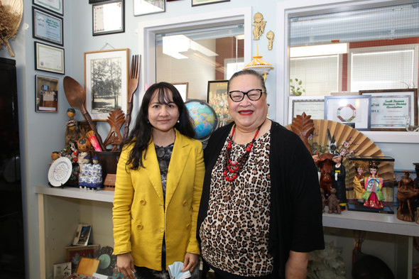 photo of two women standing in front of art display