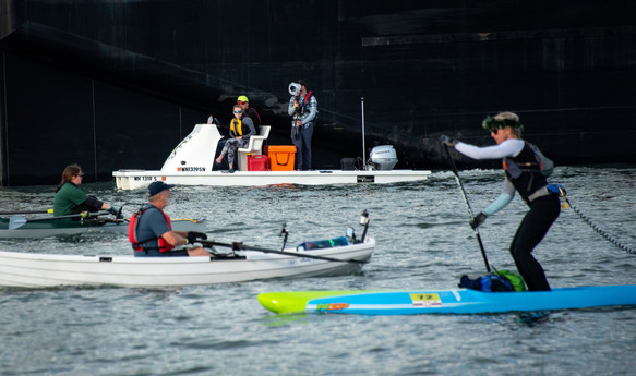 photo of people paddling a kayak and stand up paddle