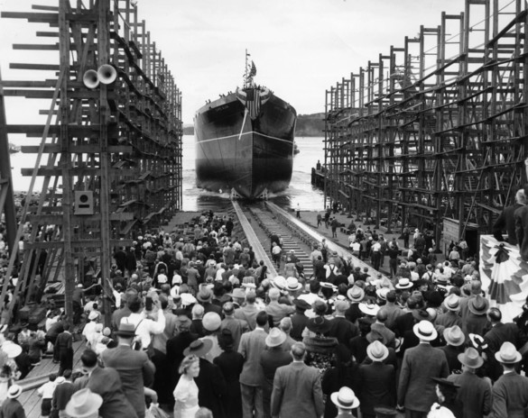 historical photo of people watching large ship being launched