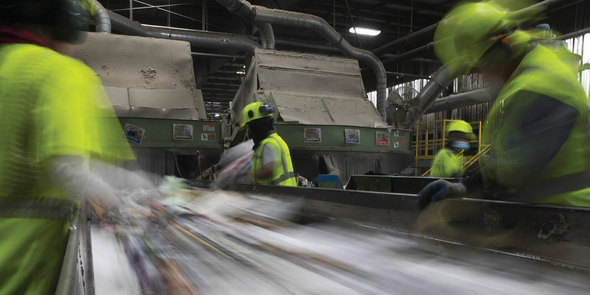 Workers sorting recycling at Waste Management recycling center