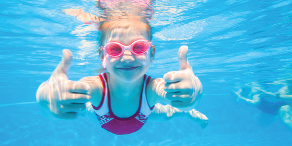 Girl swimming underwater giving thumbs up