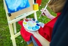 Student painting at easel outside on grass