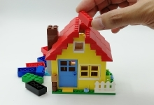 hand building house with plastic brick toys