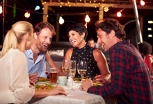 2 couples laughing over dinner table