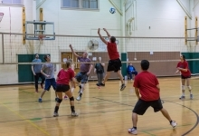 adults playing coed volleyball