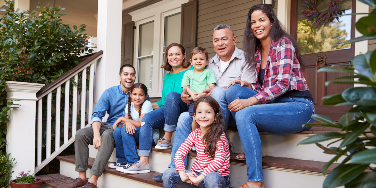 Multi-generational family sitting on front steps of house