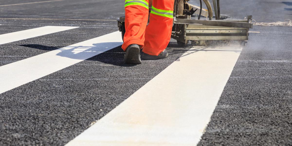 Worker painting crosswalk