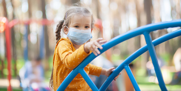 Girl with face mask playing on playground