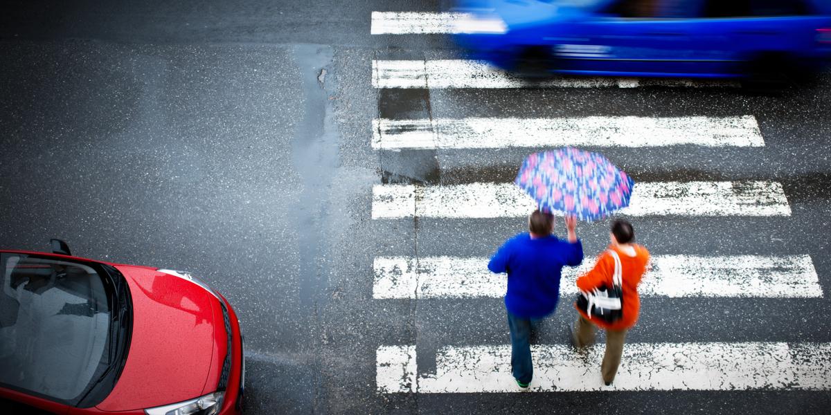 Cars running through crosswalk with pedestrians
