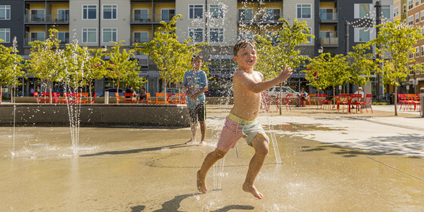 Two boys playing in the splash pad at Downtown Park