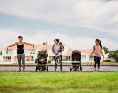 Three moms exercise in the park with their strollers and kids