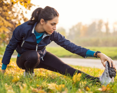 Runner stretching outdoors in a park