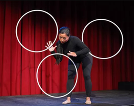 Chrysalis Circus performer Vivian Tam performing on stage with 3 hoops.