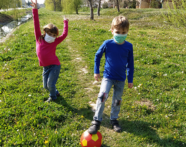 Boy and girl playing soccer wearing facemasks on a lawn.
